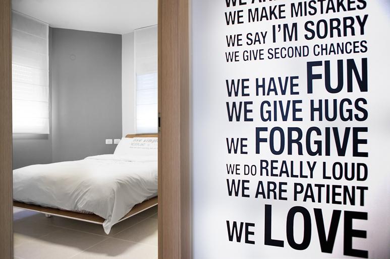 """רשימת חוקיי הבית שתוכננה ע""""י הדיירים תלויה על קיר המסדרון בכניסה לחדר שינה"""