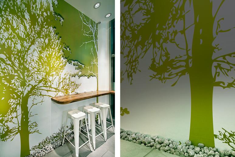 פינת ישיבה בצד אלמנטים גרפיים צמחיים המעניקים לחלל רעננות בשילוב משטח עץ וחלוקי נחל