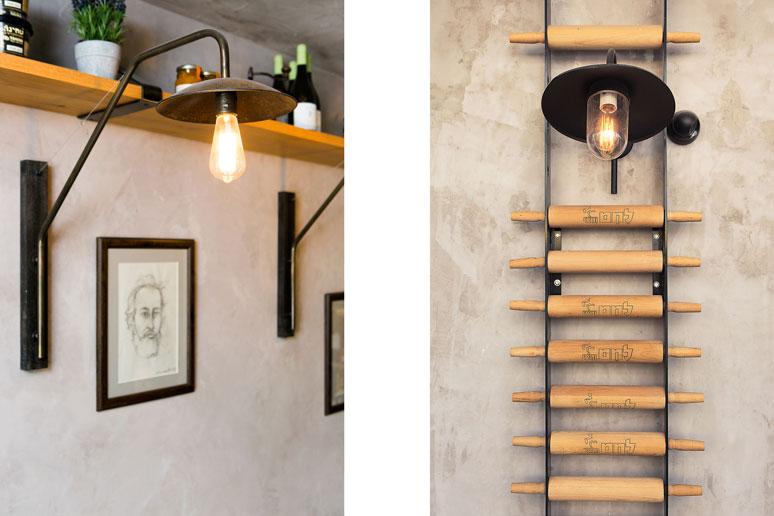 אלמנט כניסה עשוי מערוכים עליהם חרוט הלוגו, מנורת קיר תעשייתית ישנה ואיורים ידניים מעטרים את פינת הישיבה