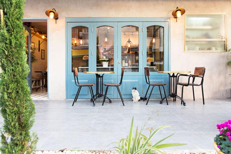 דלתות כניסה תוכננו כדלתות צרפתיות ישנות צבועות כחול ובצידן מנורות קיר מברזל מוחלד