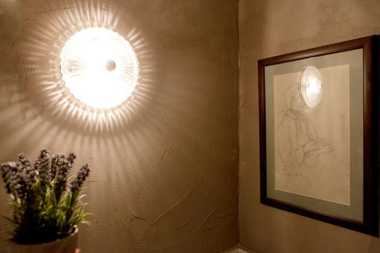 מנורת קיר מזכוכית ישנה בצד איור ממוסגר על קיר בטון מחוספס