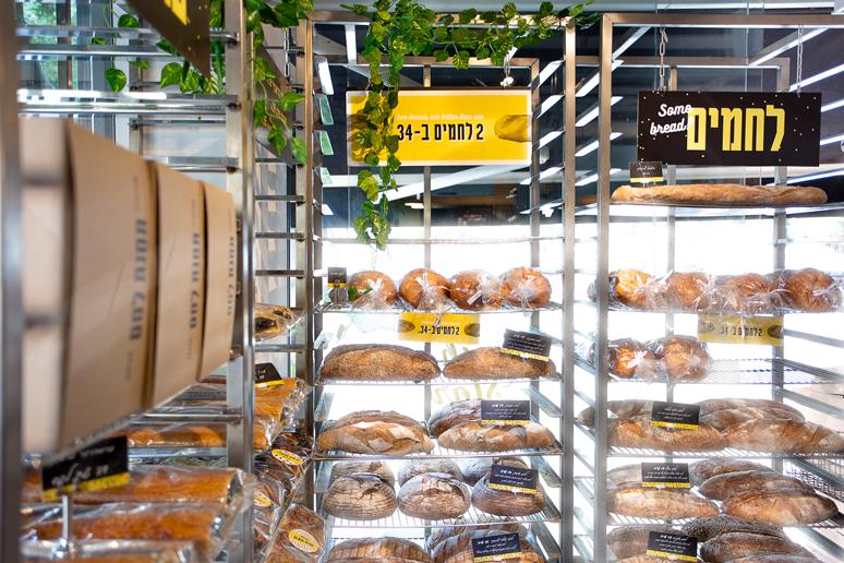 עגלות נירוסטה לתצוגת כיכרות לחם הוצבו בצמוד לוויטרינת הכניסה ויצרו חזית קלילה ואוורירית המבטלת את החיץ בין החוץ לפנים