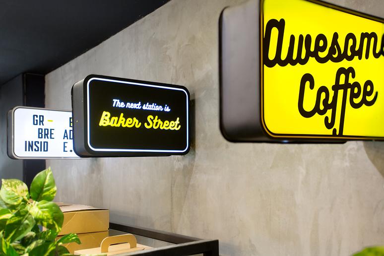 שלטי רחוב מוארים הותקנות מעל מדפי התצוגה בעיצוב גרפי בשפת המותג בצבעי שחור לבן צהוב