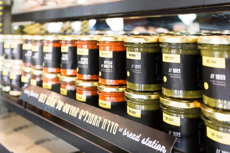 רטבים, ממרחים, ושלל מוצרים מוצגים על מדפי תצוגה עשויים ברזל צבוע שחור בשילוב רשת אקספנדד שטוחה