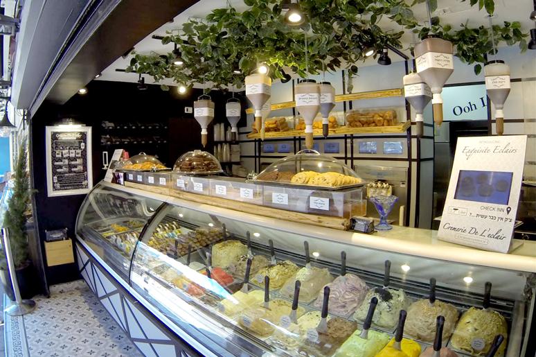 שתי ויטרינות גדולות לאורך כל החזית מציעות מגוון רחב של גלידות, בצידן תפריטי קיר, מדפי אחסון מזכוכית ומאחוריהן מכונות גלידה ומסכי מידע