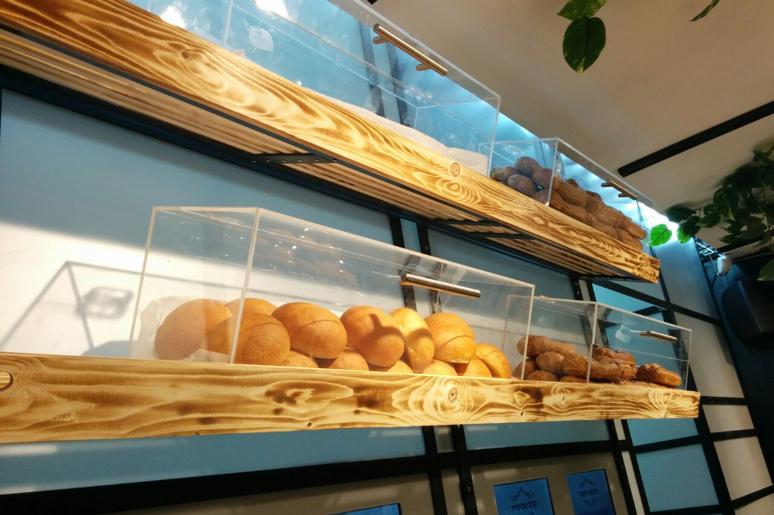סביב מכונות הגלידה תוכננה מחיצה עשויה ברזל ופרספקס ועליה נתלו מדפי עץ ובתוכם קופסאות פרספקס המכילות אקלרים, מאפים ועוגיות