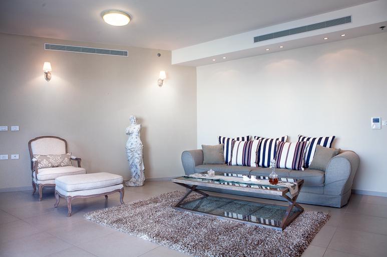 עיצוב סלון בדירת קבלן תוך שמירה על צבעוניות רכה ומלטפת ויצירת פינות ישיבה מפנקות הצופות אל הנוף
