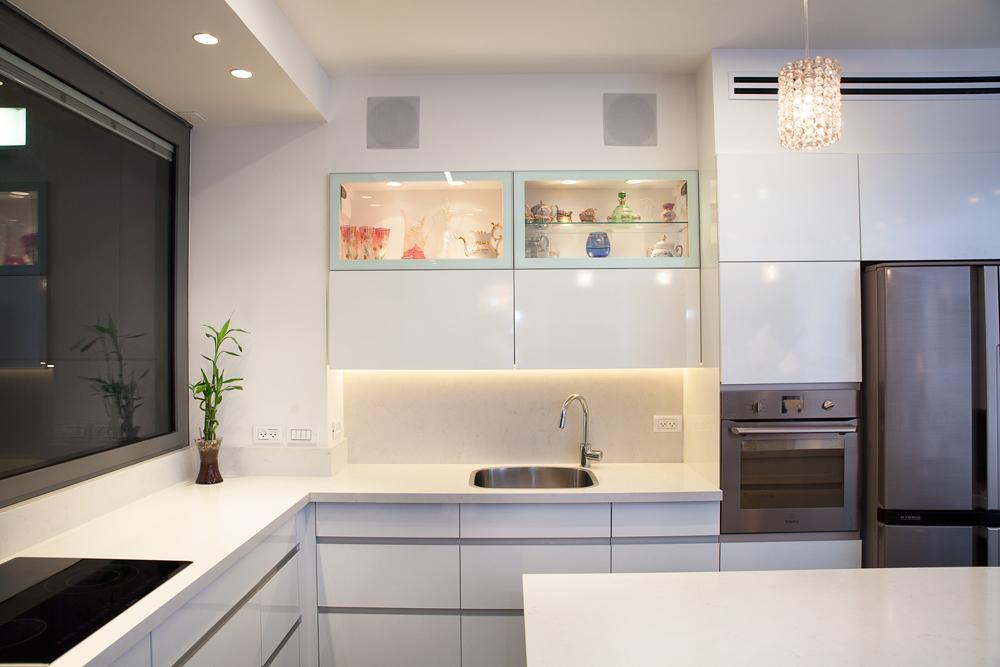 עיצוב מטבח מודרני בשילוב אי רחב, משטח שיש קיסר, קלפה משולבת זכוכית חלבית ושקופה ומשחקי תאורה בהתאם