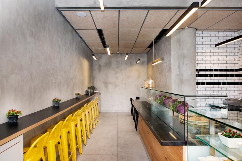עיצוב פסטה בר בסגנון תעשייתי מודרני המשלב בטון, מתכת, עץ, ונגיעות פח צבוע צהוב