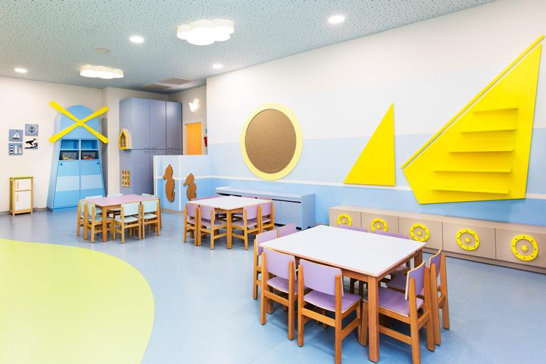 שולחנות וכסאות עשויים עץ בגוונים שונים בכיתת הלימוד לילדים בגן