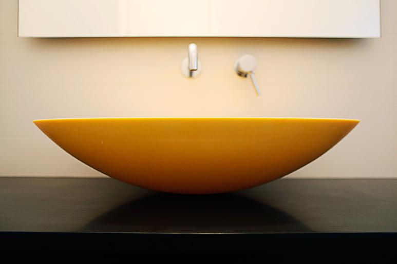 כיור קוריאן צהוב מונח על גבי משטח קוריאן שחור  בארון חדר הרחצה