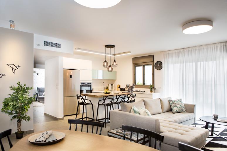מבט מפינת האוכל אל המטבח והסלון מציג חלל מואר במגוון צורות