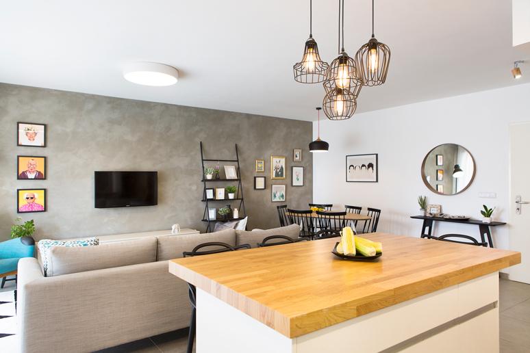 מנורות רשת תעשייתיות מעל אי ישיבה מרכזי עם משטח עץ אלון על גבי ארון מטבח לבן עשוי פורמיקה