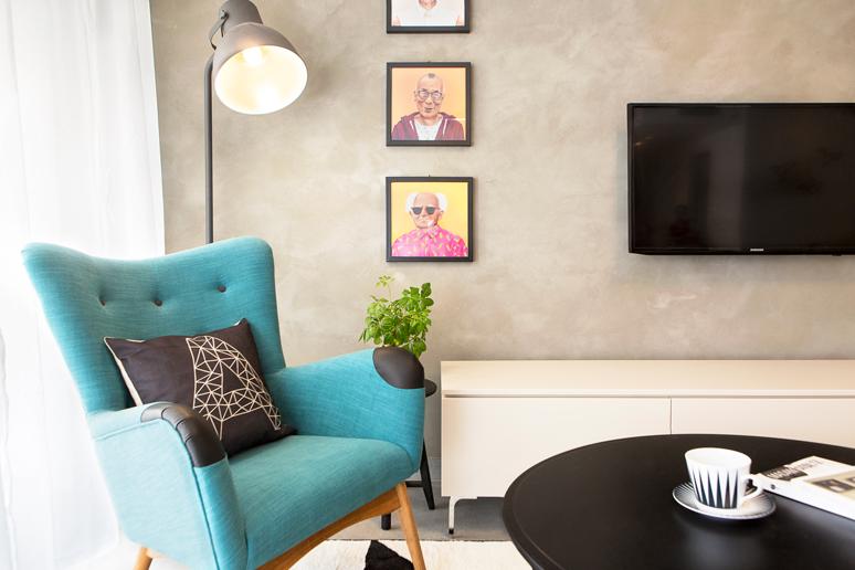 פינת קריאה הכוללת כורסא כחולה, מנורת עמידה ותמונות מנהיגי עולם היפסטרים