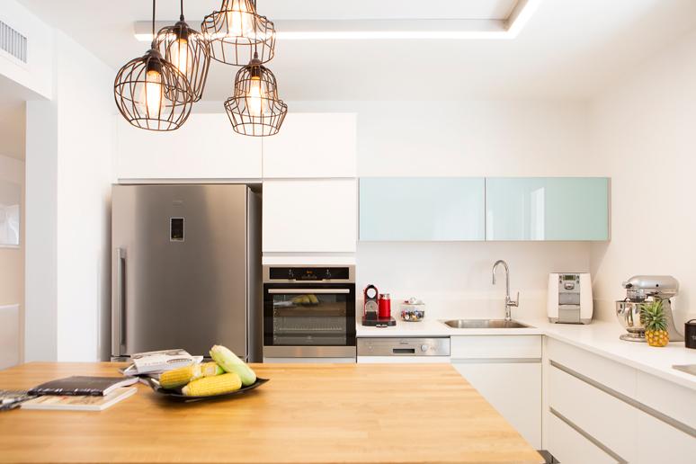 מטבח עשוי פורמיקה לבנה שיש לבן חזית קלפה בגימור זכוכית בגוון תכלת פרופיל תאורה במטבח מותאם למבנה המטבח והרבה משטחי עבודה