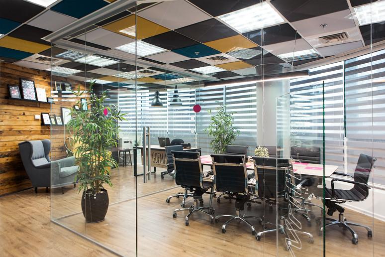 חדר הישיבות מעוצב הממוקם בכניסה למשרד סגור בקירות זכוכית שקופים בשילוב גרפיקה עדינה