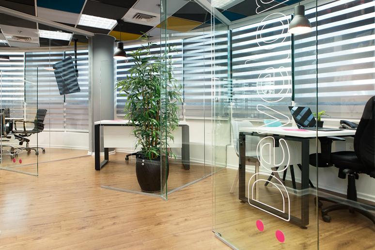 מבט אל המשרדים הפרטיים. רגלי שולחן צבועות שחור גרפיט ומשטח מלמין לבן
