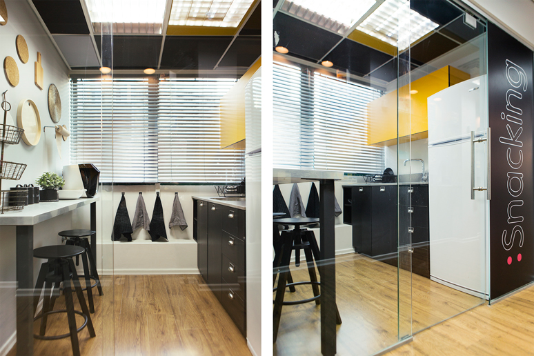 המטבחון במשרד - קלפה צהובה, כסאות בר שחורים, קיר דקורטיבי הכולל מערוך וכלי מטבח ומיתוג חיצוני