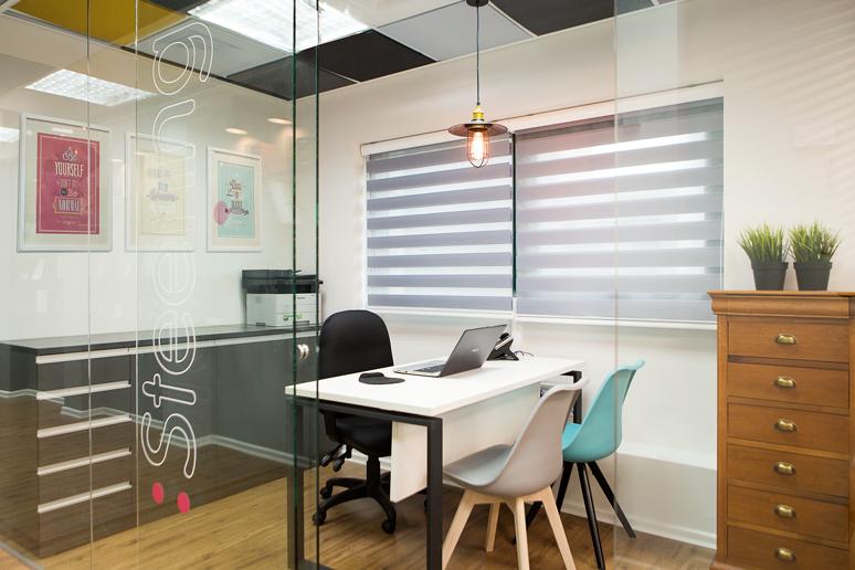 משרד סגור עם מחיצת זכוכית ממותגת, כסאות אורח בגוונים משתנים וגוף תאורה תעשייתי עם נורת פחם
