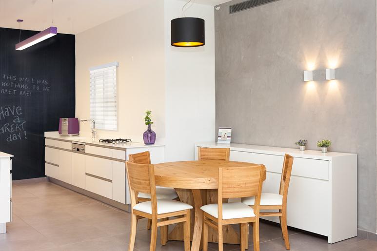 עיצוב פינת אוכל בסגנון מודרני תוך שימוש בעץ אלון ושידת אחסון בצבע שלייפלק בתנור על רקע קיר בגמר שליכט דמוי בטון