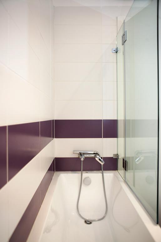 עיצוב אמבטיה בפריסה מעניינת של אריחי סטנדרט בגוון סגול ולבן