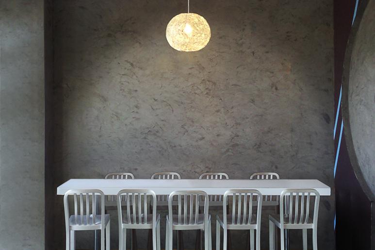 חיפוי דמוי בטון הממשיך מהקיר אל רצפת אזור הישיבה משווה לחלל מראה תעשייתי עדין