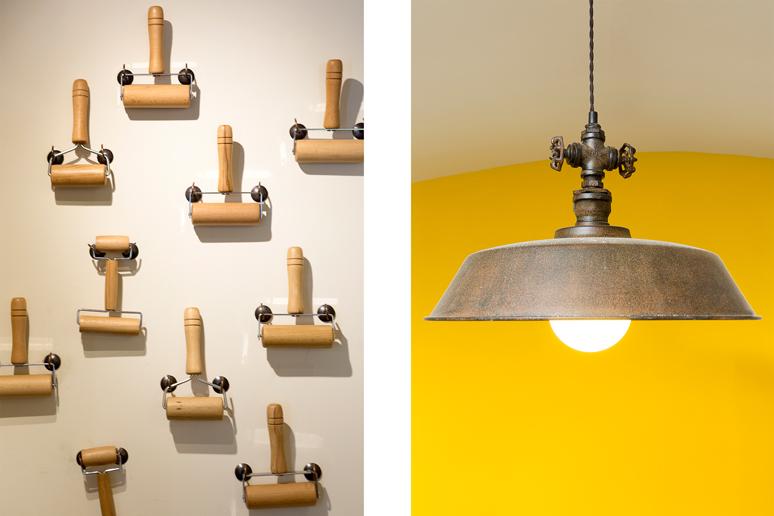 גוף תאורה עשוי מתכת מיושנת עם מחבר בצורת ידית ברז ישנה וקיר מערוכים דקורטיבי