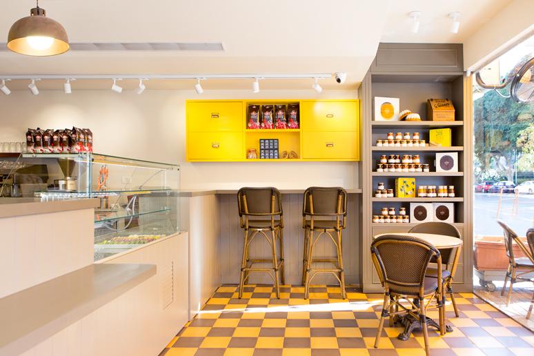 עמדת שירות לקפה הכוללת דלפק וארון אחסון למפיות סוכרים וכדומה בצד עמדת תצוגת מוצרים ופינת ישיבה