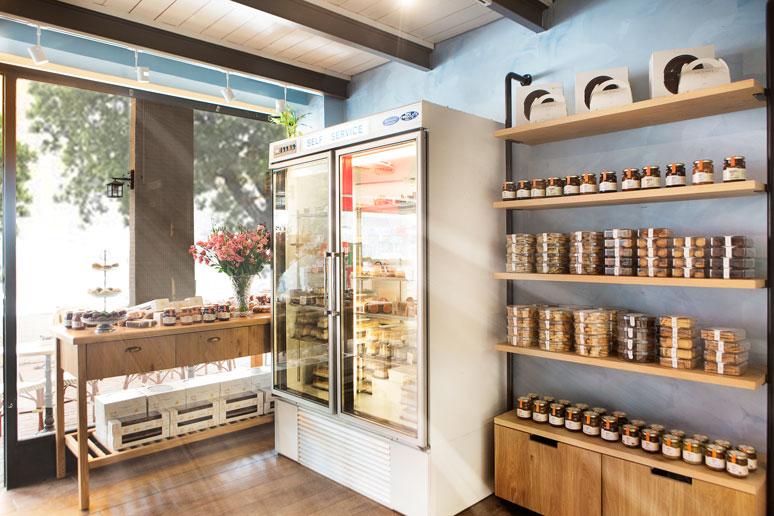 מקרר תצוגת עוגות מלא כל טוב, תקרת גלריה עשויה מתכת ועץ, רצפת פרקט עץ ופסי צבירה עם ספוטים של תאורה חמה