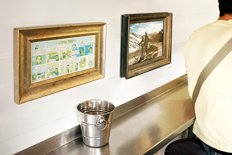 תמונות נוסטלגיות שופצו ומוסגרו במסגרות בגדלים וסגנונות שונים ליד עמדת ההמתנה