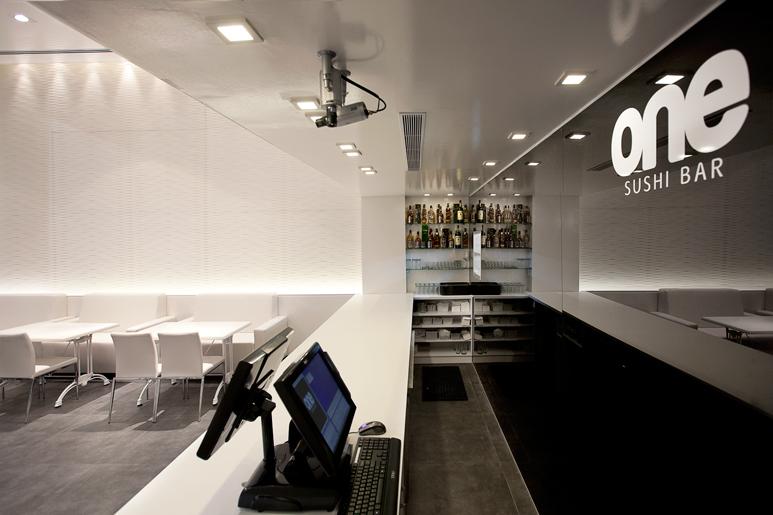 חיפוי זכוכית שחורה מודפסת בקיר המפריד בין המטבח לדלפק ההגשה
