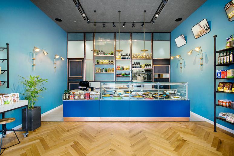 מעדנית בוטיק המוכרת אוכל מוכן עוצבה בסגנון אירופאי מאופק בגווני כחול בשילוב נחושת ופליז