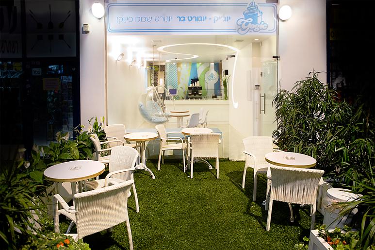 עיצוב חזית היוגורטיה בעזרת משטח דשא, אדניות ופינות ישיבה